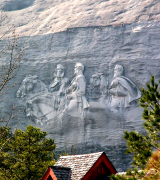 "The Carving: the largest high relief sculpture in the world, the Confederate Memorial Carving, depicts three Confederate heroes of the Civil War, President Jefferson Davis and Generals Robert E. Lee and Thomas J. ""Stonewall"" Jackson. The entire carved surface measures three-acres, larger than a football field. The carving of the three men towers 400 feet above the ground, measures 90 by 190 feet, and is recessed 42 feet into the mountain. The deepest point of the carving is at Lee's elbow, which is 12 feet to the mountain's surface. Stone Mountain is a granite dome located in Stone Mountain, Georgia, a suburb of Atlanta. It is the world's largest exposed mass of granite. At its summit, the elevation is 1,683 feet (513 m) amsl and 825 feet (251.5 m) above the surrounding plateau. It is well-known not only for its geology, but also for the enormous bas-relief on its north face, the largest bas-relief in the world. Three figures of the Confederate States of America are carved there: Stonewall Jackson, Robert E. Lee, and Jefferson Davis. The mountain was the site of the founding of the second Ku Klux Klan in 1915, and the Klan was intimately involved in the design, financing, and early construction of the monument. However, they were not the originators of the idea"